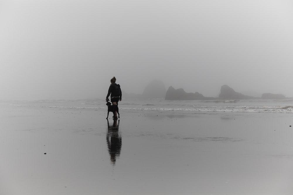 man walking in seashore beside dog