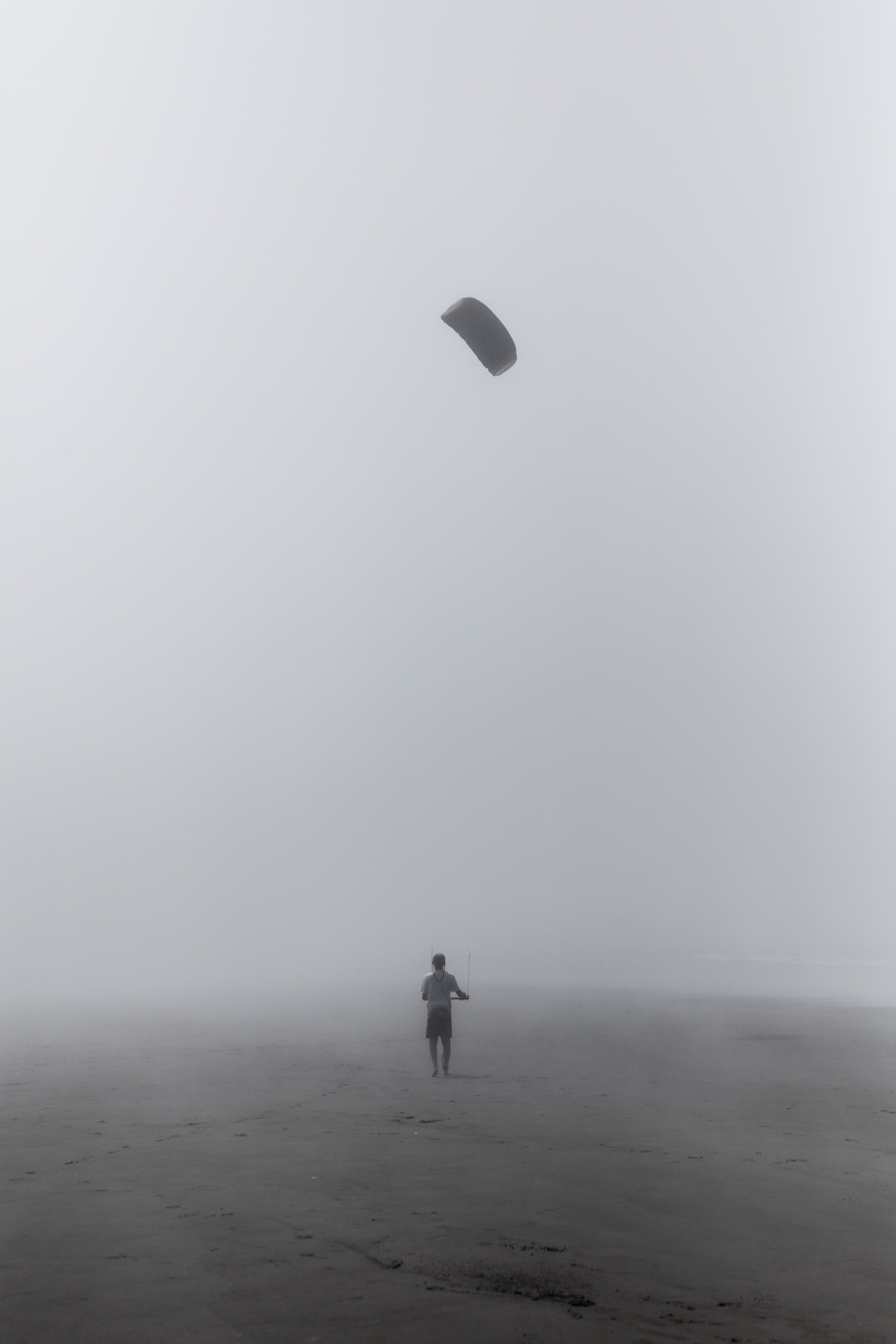 grayscale photography of person flying kite