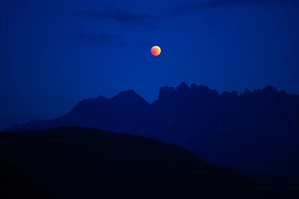 lunar eclipse with silhouette mountain
