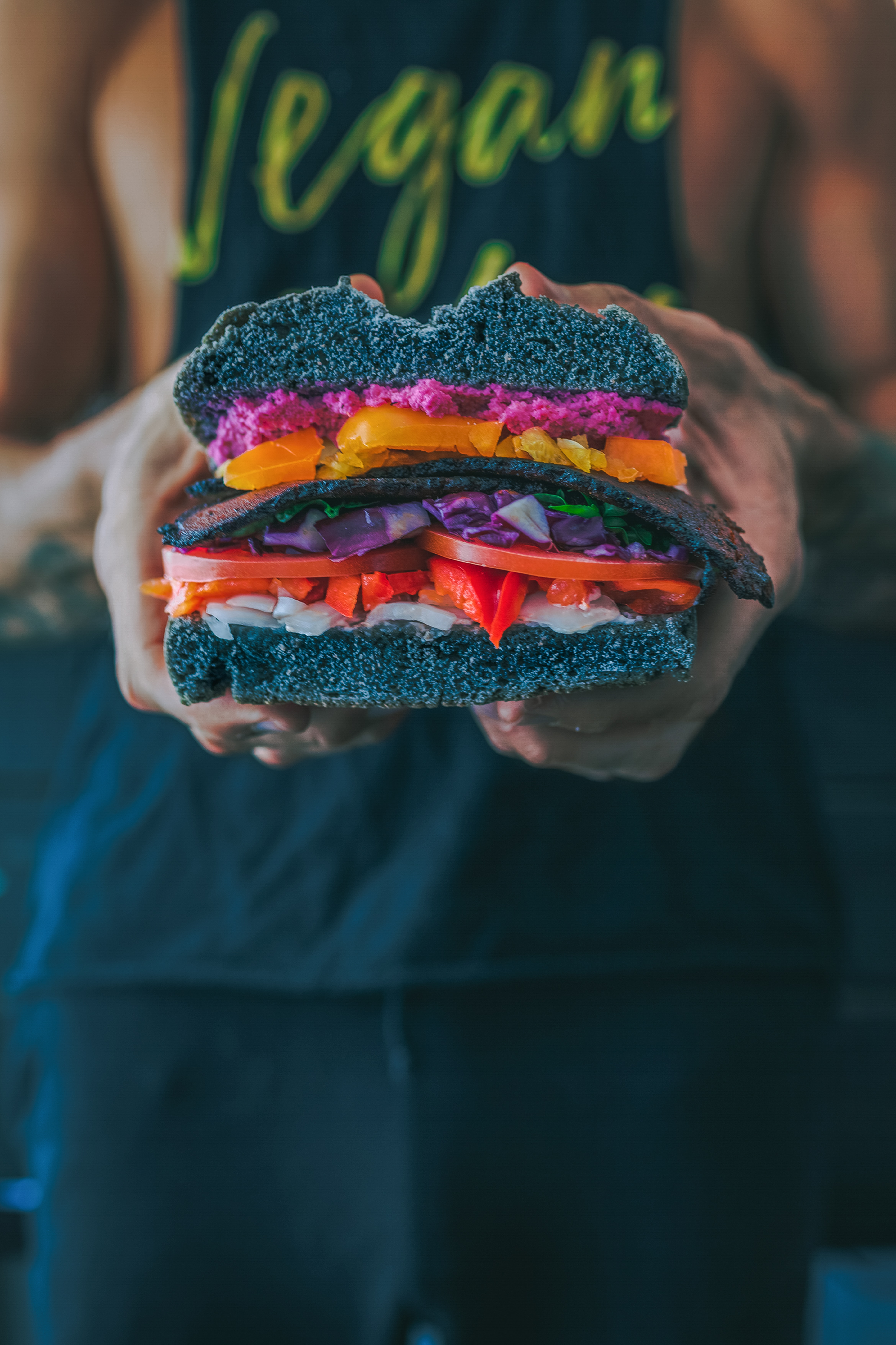 person holding meat sandwich with sliced tomatoes, onions, and grilled meat