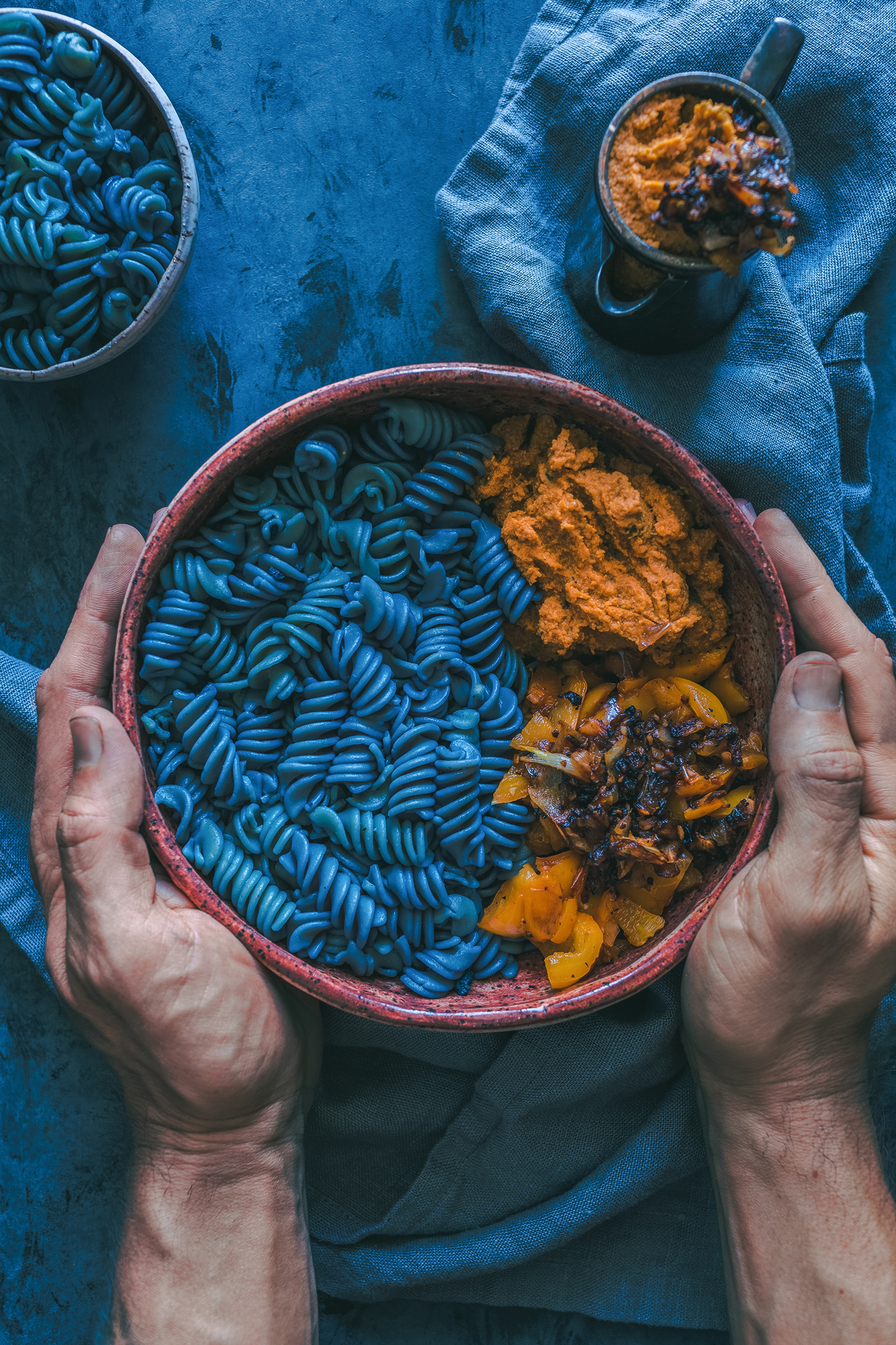person holding bowl of pasta dish