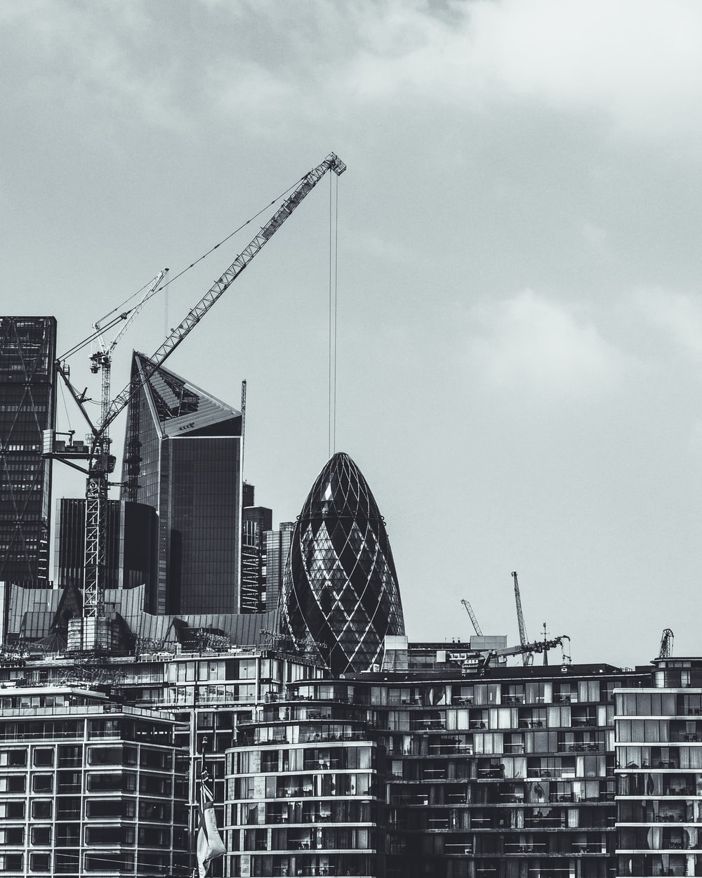 grayscale photography of 30 St.Mary Axe near on building