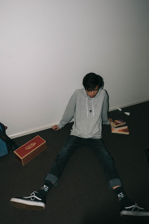 man sitting on black mat beside white wall
