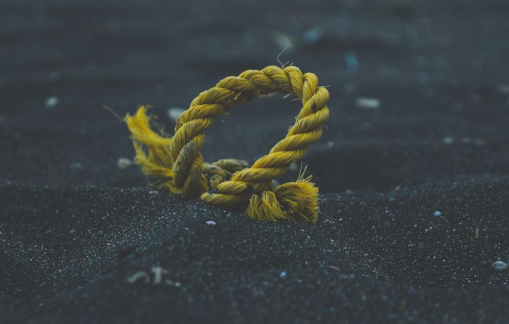 yellow rope on black sand
