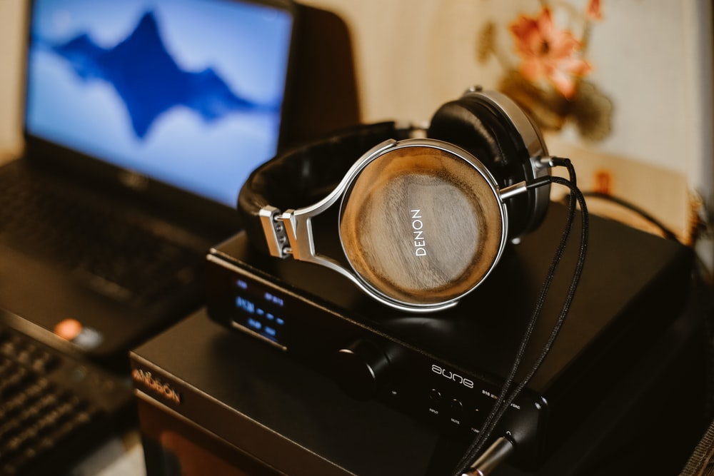 brown corded headphones on black electric device