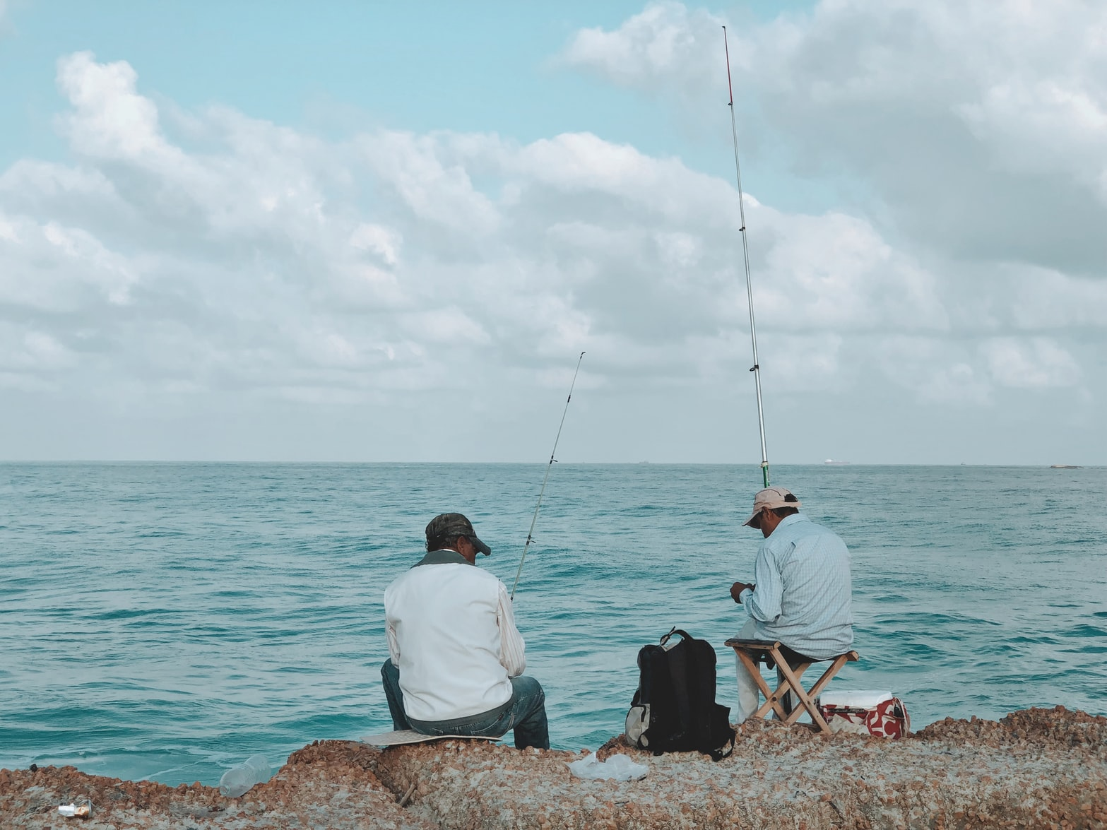 2 men at the shore is doing some fly fishing at the ocean