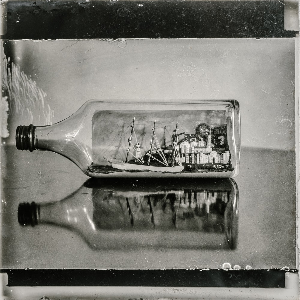 grayscale photo of boat in bottle table decoration