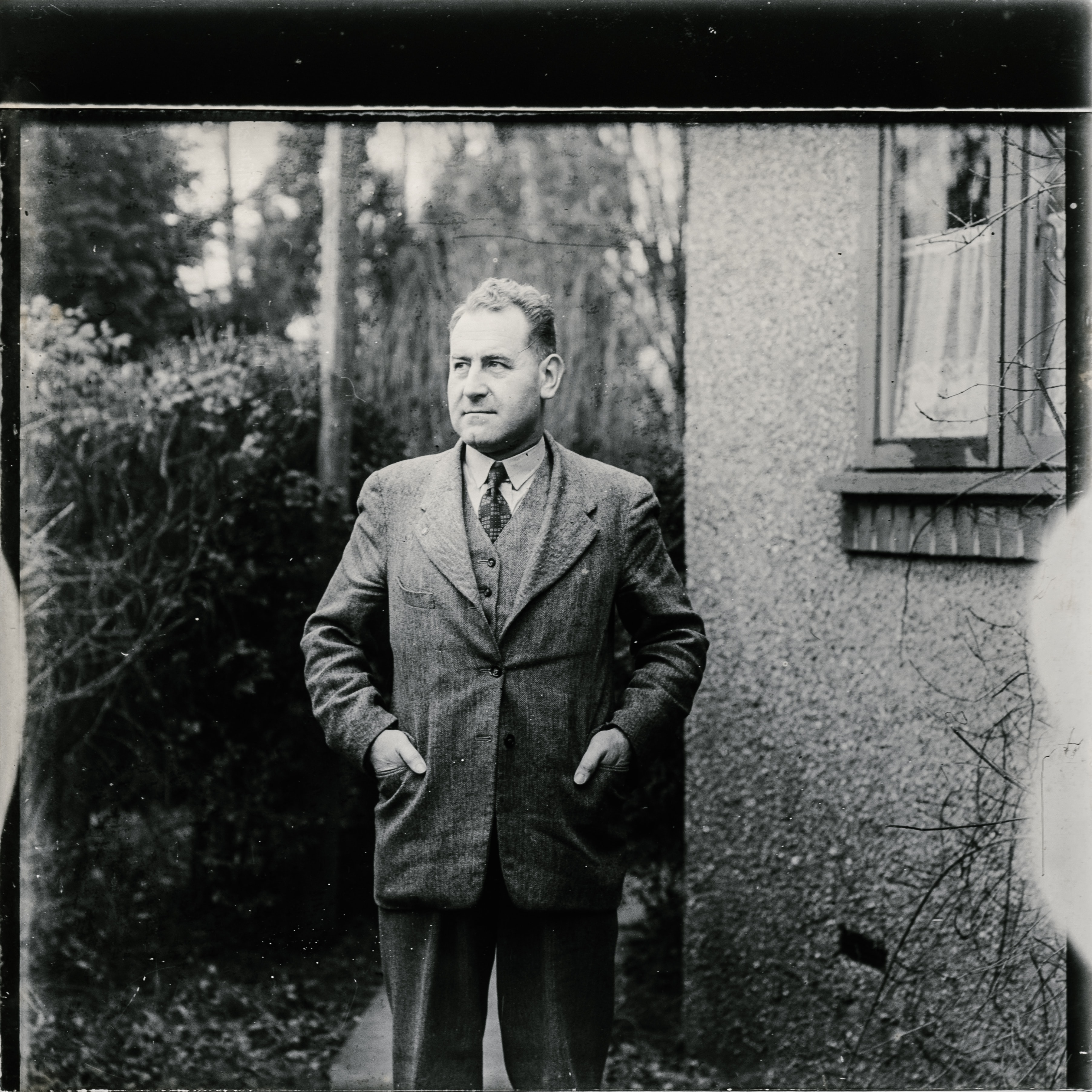 grayscale photo of man wearing suit standing beside wall with mirror