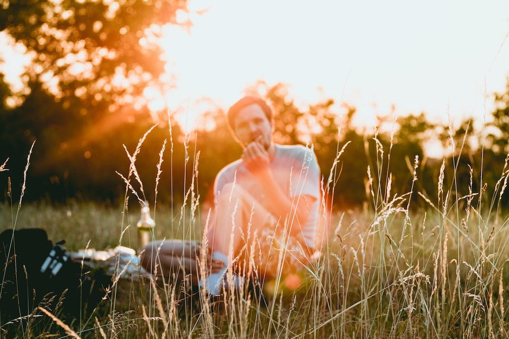 man sitting on green grass eating food during sunrise