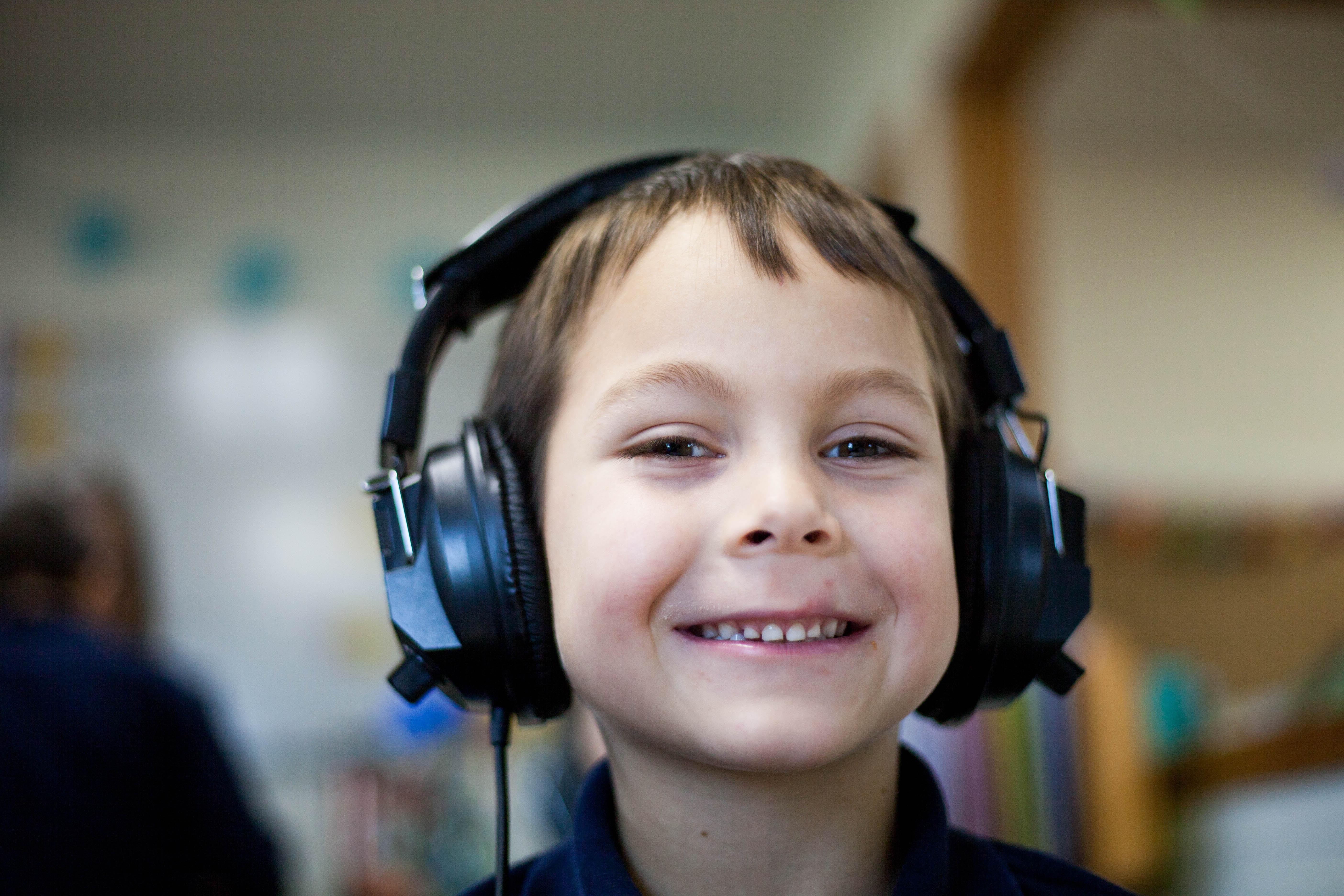 selective focus photography of boy wearing corded headphones