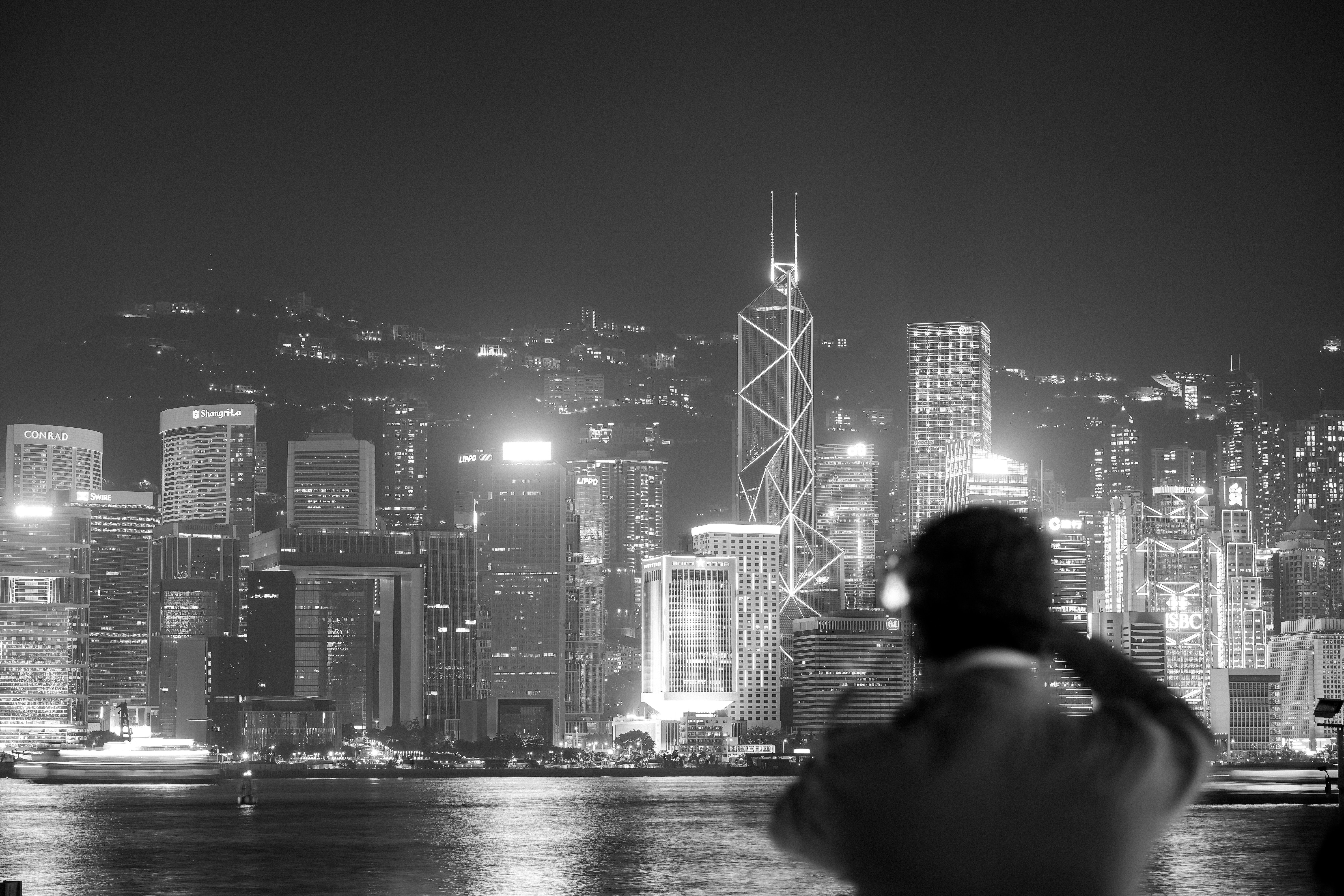 grayscale photography of person staring at city buildings