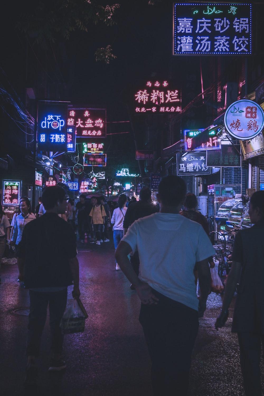 man wearing white shirt walking in the middle of street