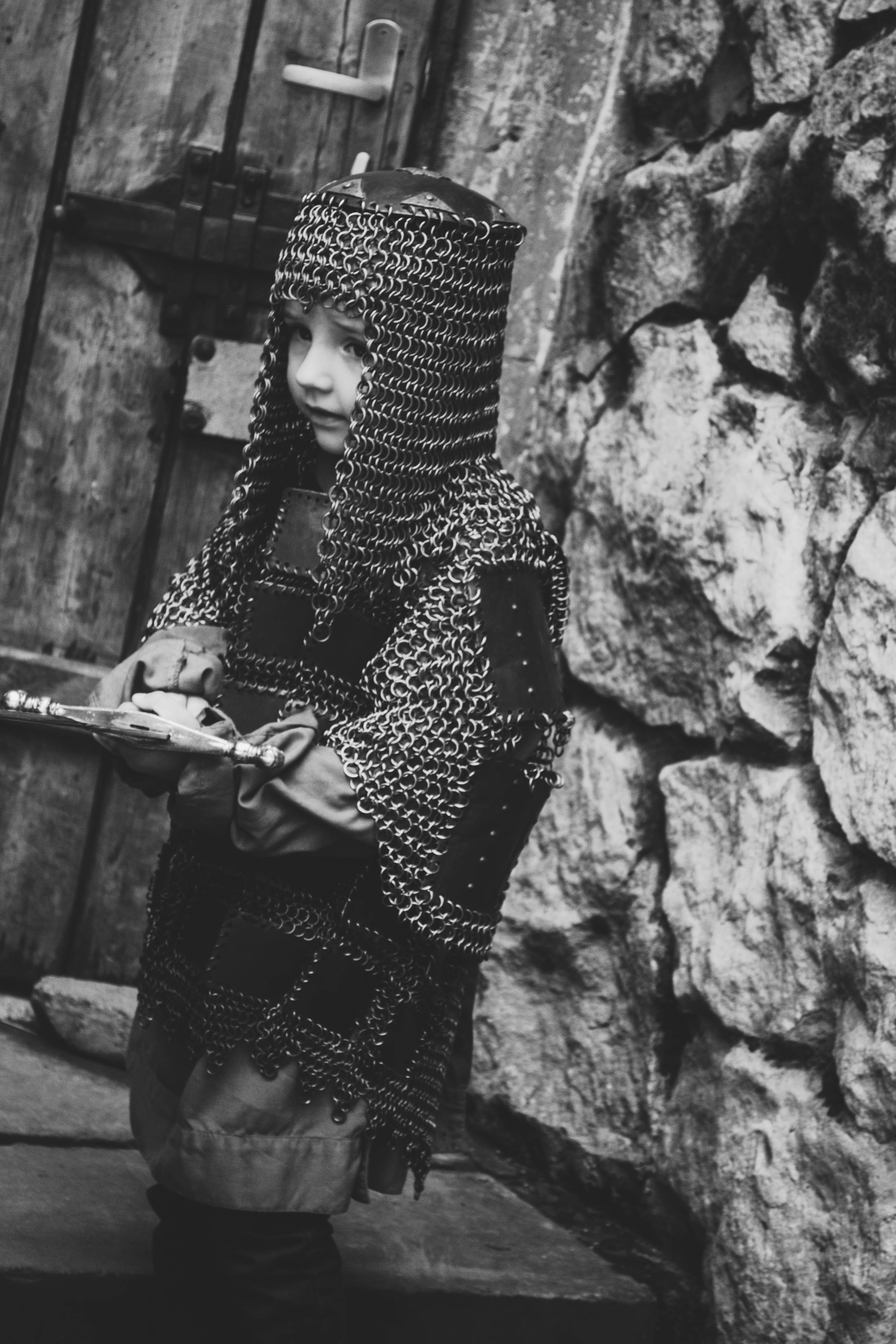 grayscale photo of child wearing chain mail
