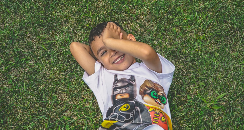 boy laying on green grass
