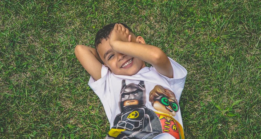 緑の草の上に横たわっている少年