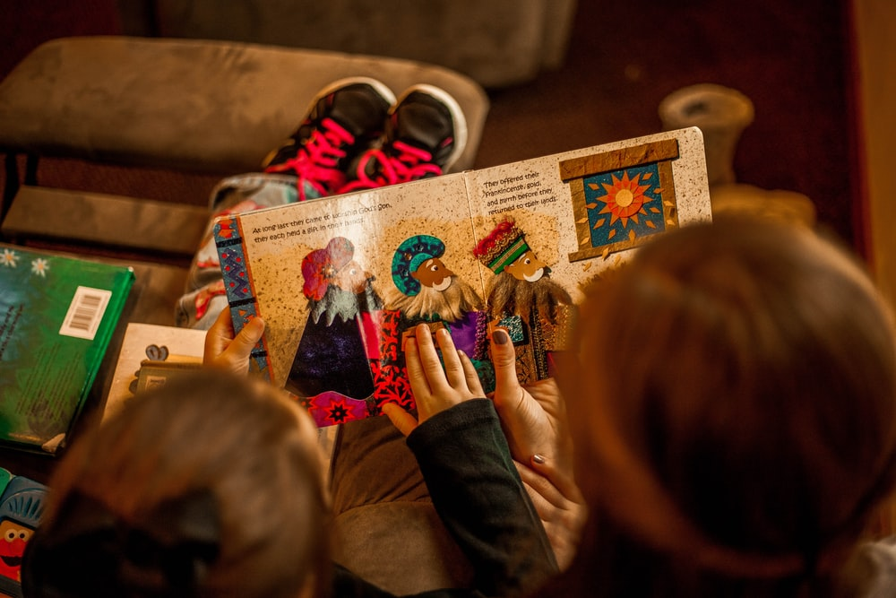 two childrens reading book while sitting on brown sofa