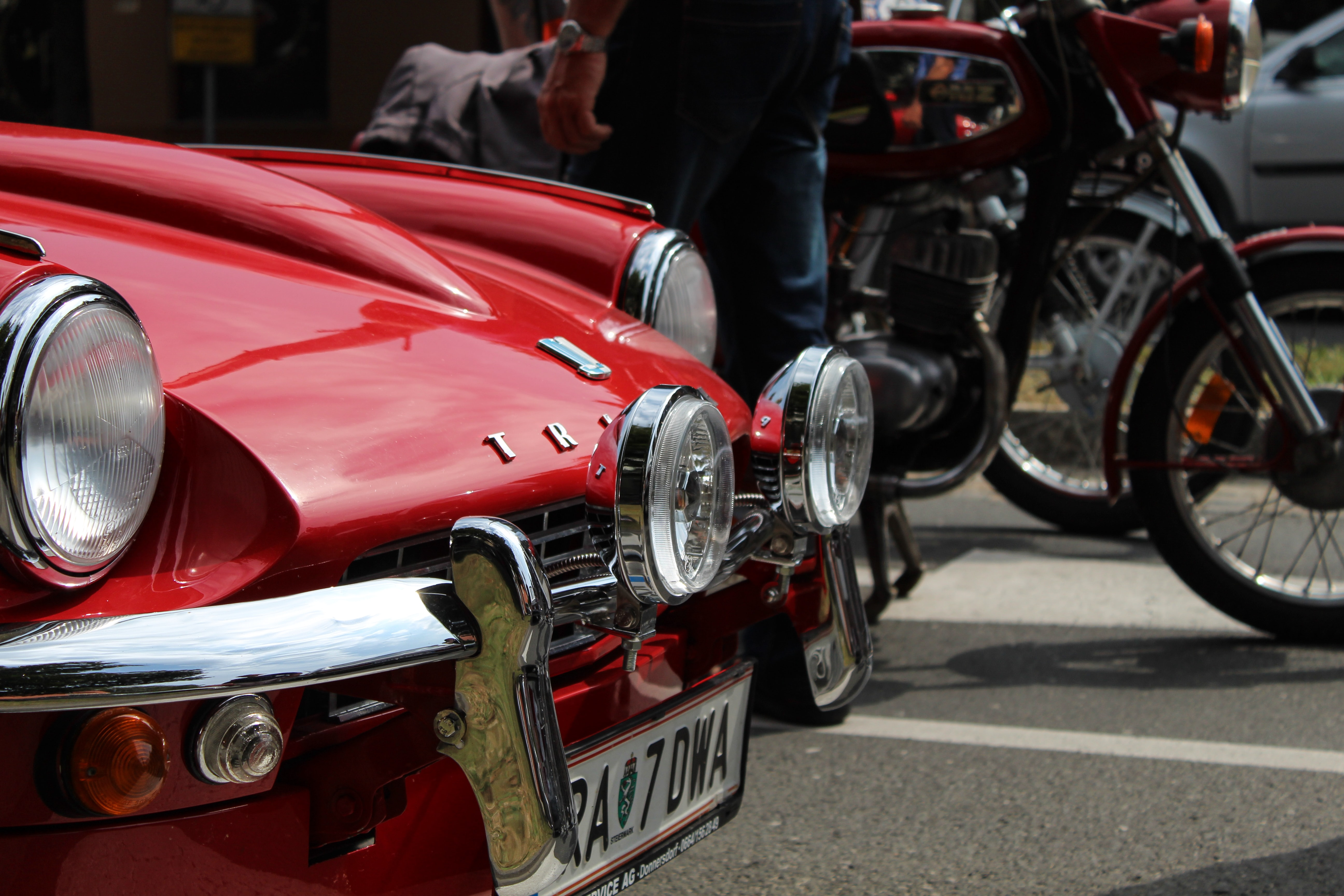 vintage red car near person driving motorcycle during daytime