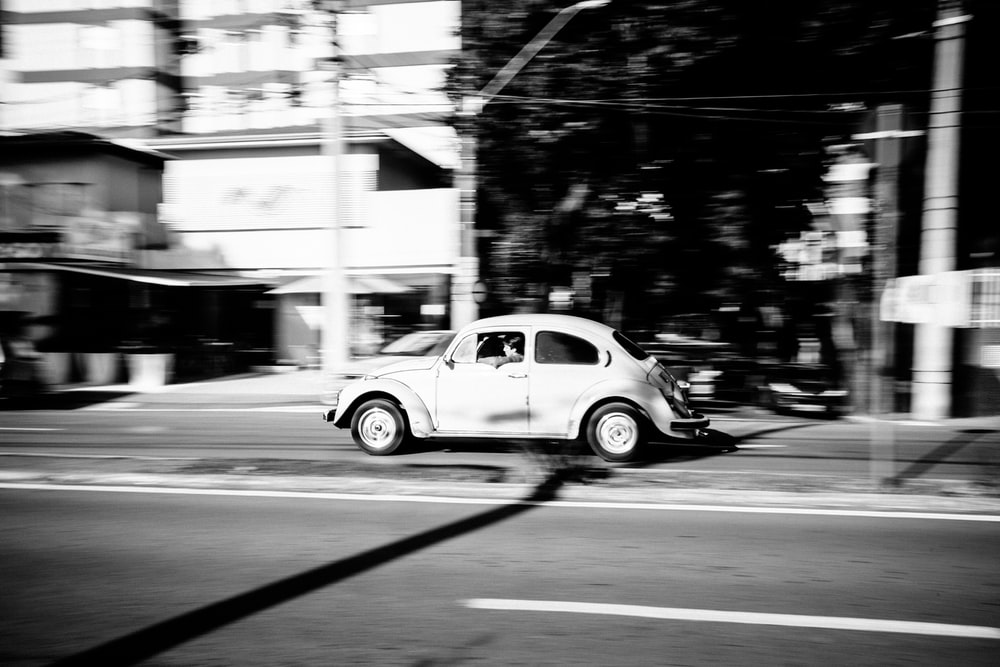grayscale photo of white Volkswagen Beetle car running on gray road