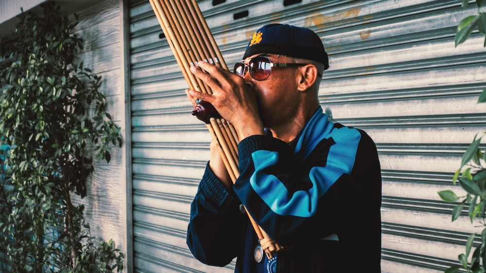 man playing wood wind instrument outdoors