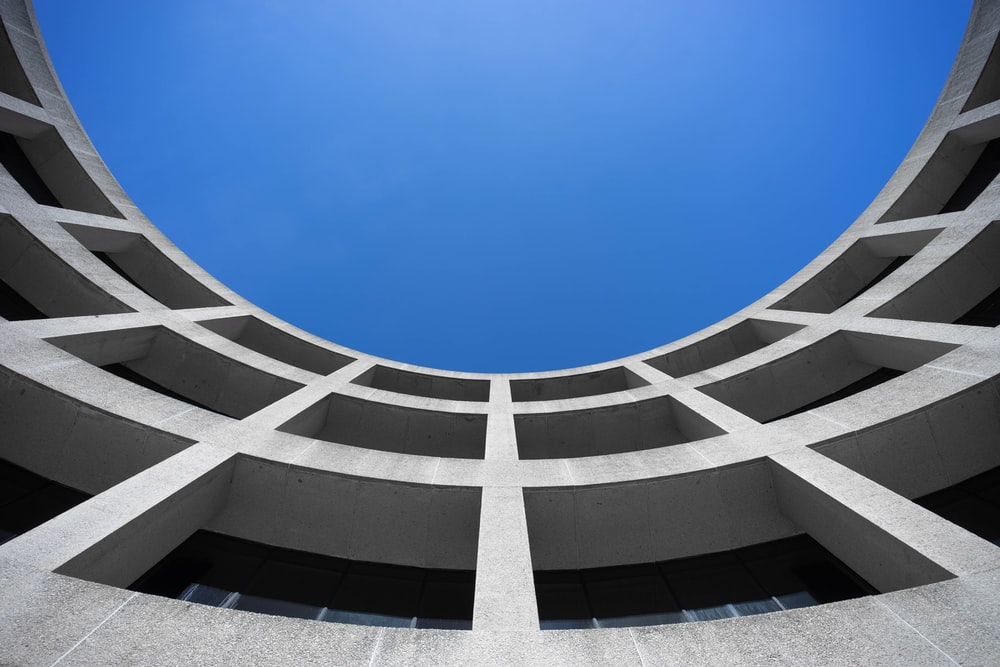 low angle photography of gray concrete building at day time