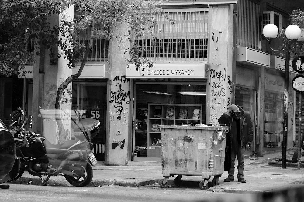 grayscale photography of man standing beside trash can