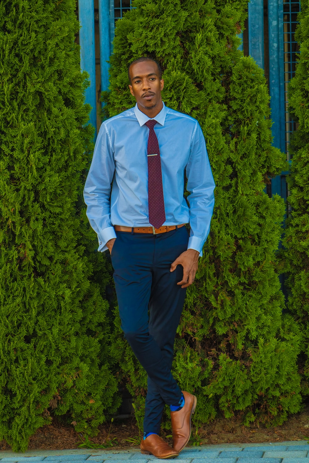 man in blue dress shirt and pants near green leafed plants