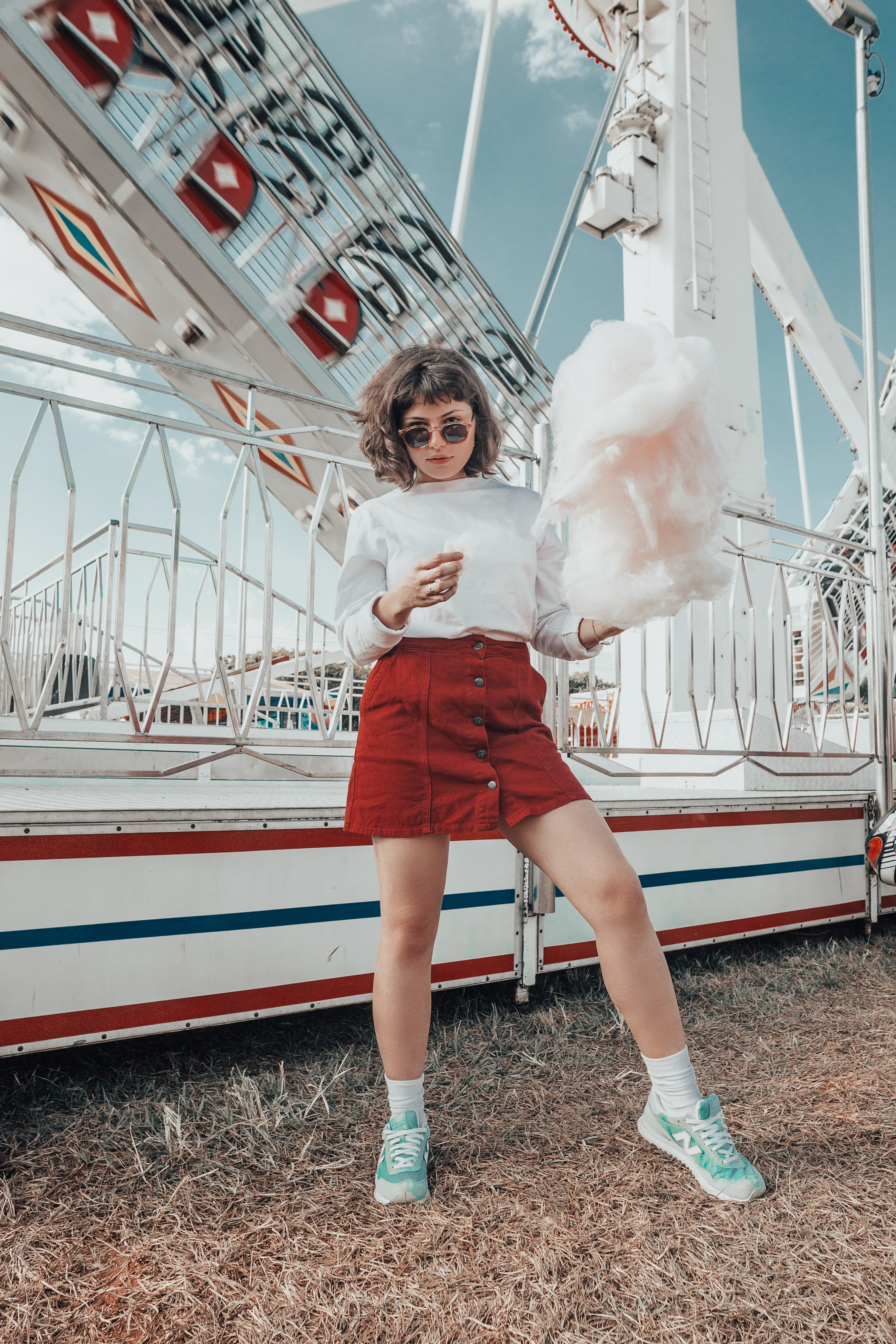 woman in white long-sleeved top holding cotton candy