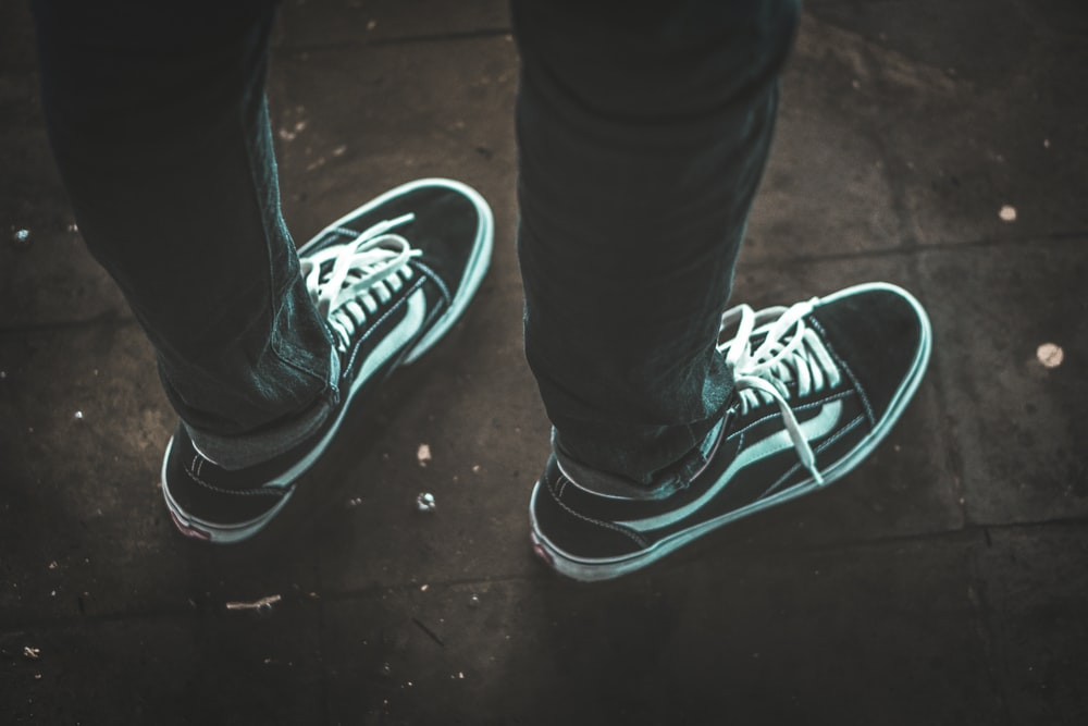 person wearing black-and-white Vans Old-Skool senakers