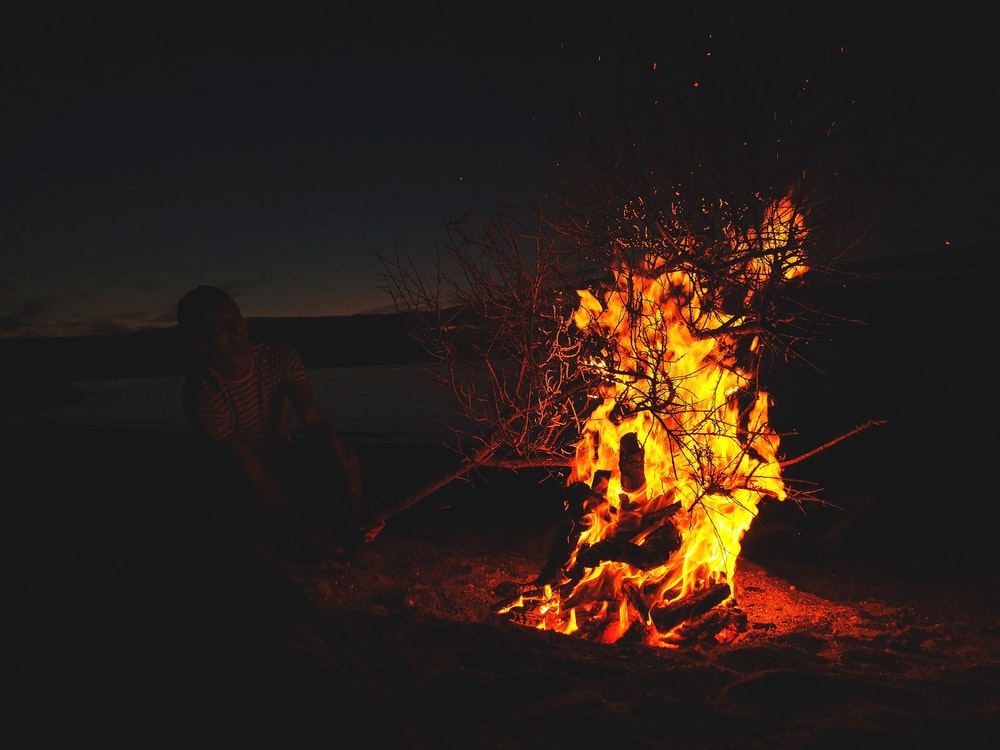 man in front of lighted bonfire