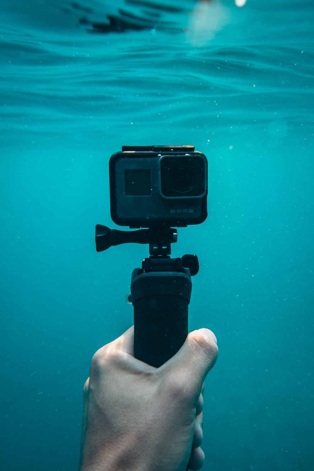 person holding action camera in underwater