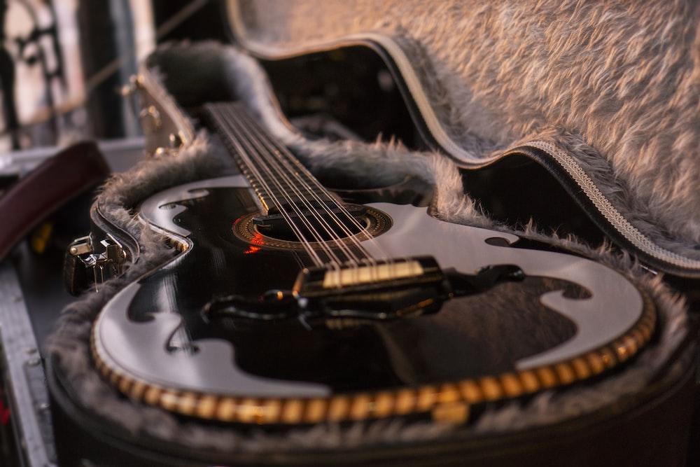 closeup photo of gray and black guitar