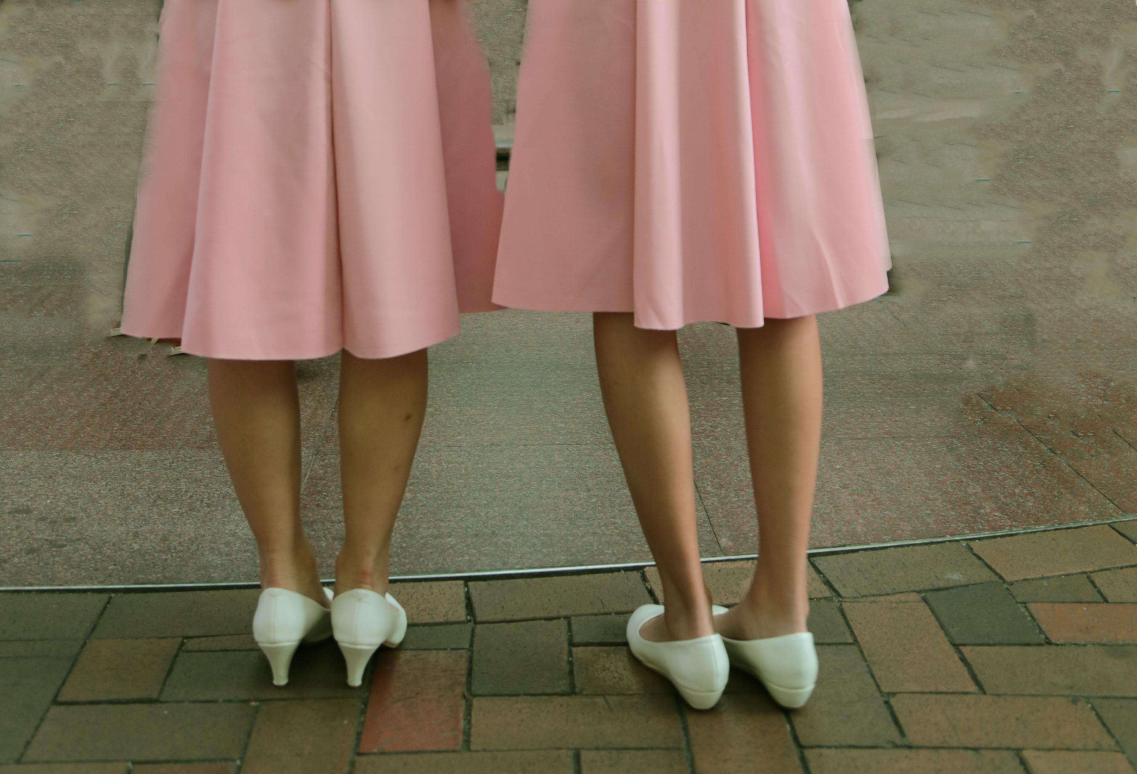 two women wearing pink skirts