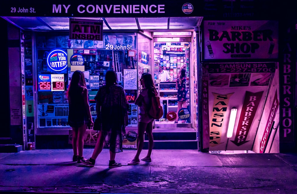 three woman standing in convenience storefront