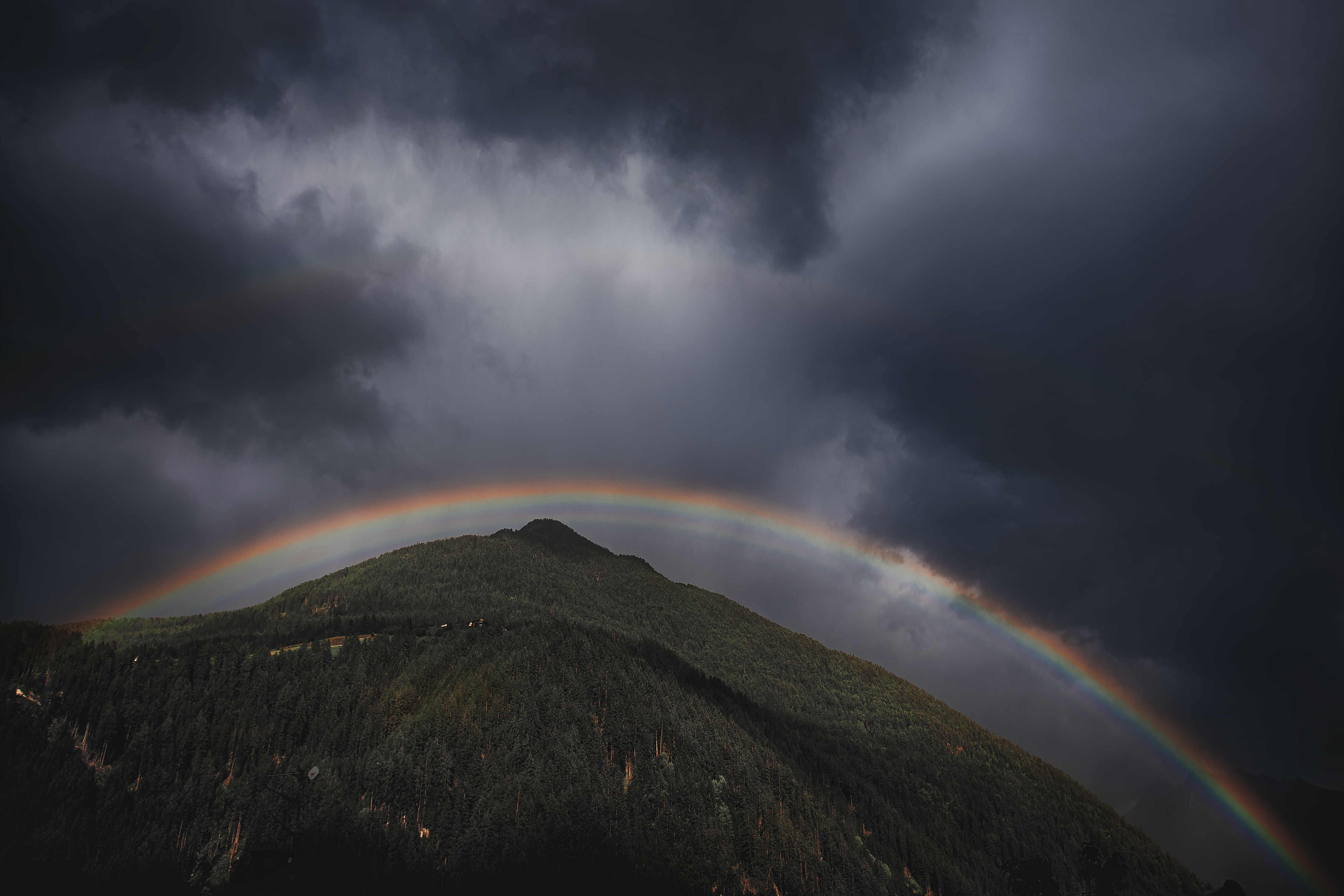 low angle photo of mountain under rainbow and cloudy sky at daytime