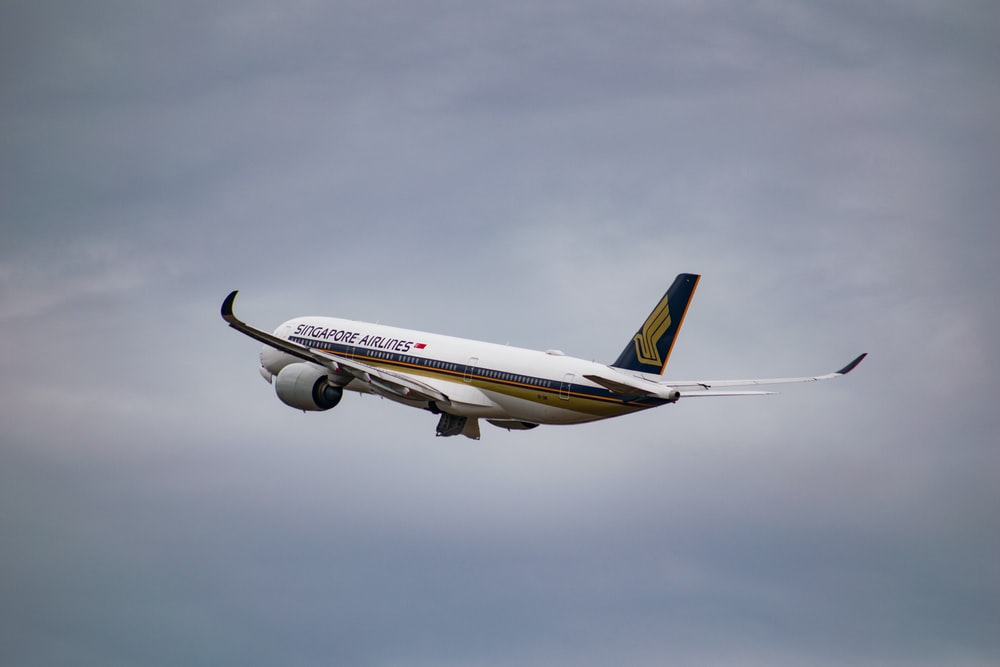white Singapore Airlines airplane flying during cloudy day