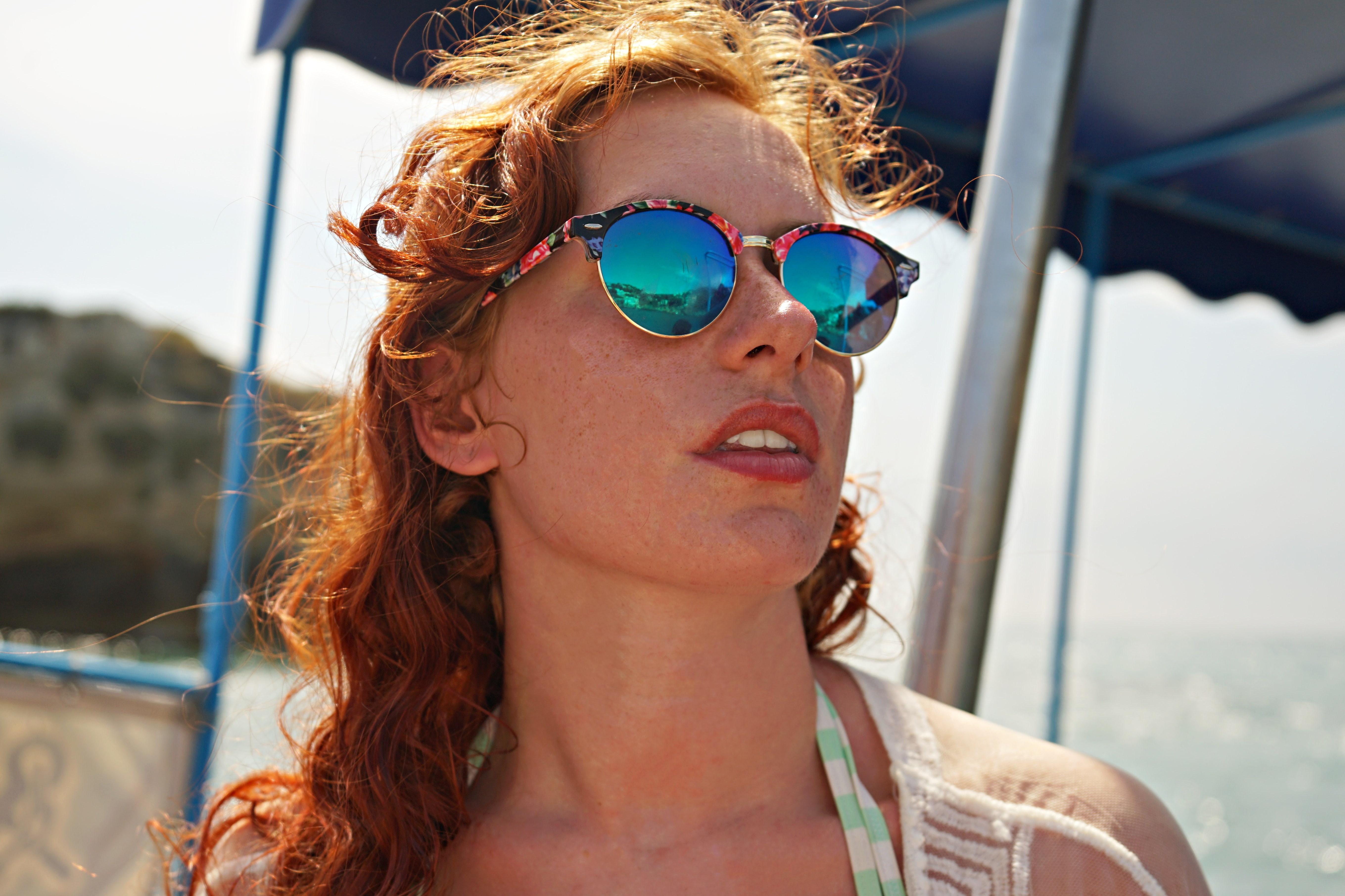 selective focus photo of woman wearing sunglasses on seashore