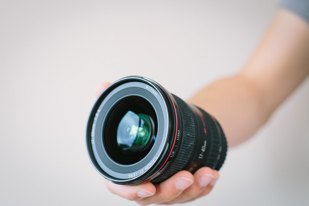 person holding black macro lens