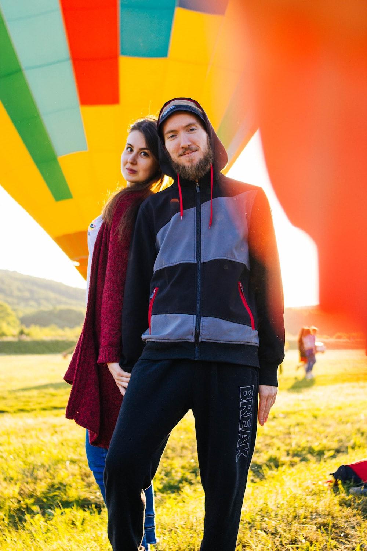 man and woman standing near hot air balloons