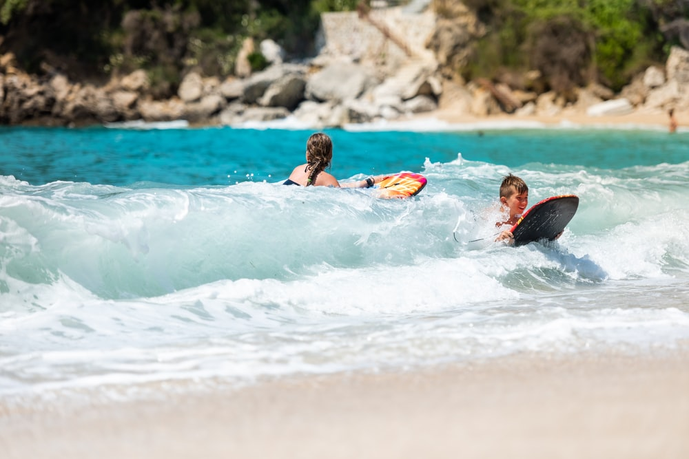 man and woman using body boards in body of water