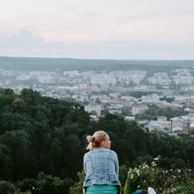 woman sitting overlooking city buildings during daytime