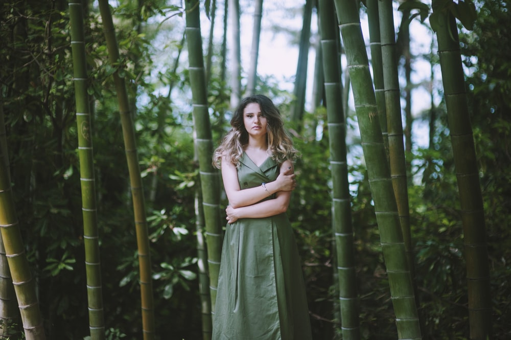 woman in green dress near bamboo trees