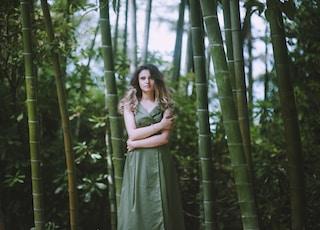 woman in green dress near bamboo trees