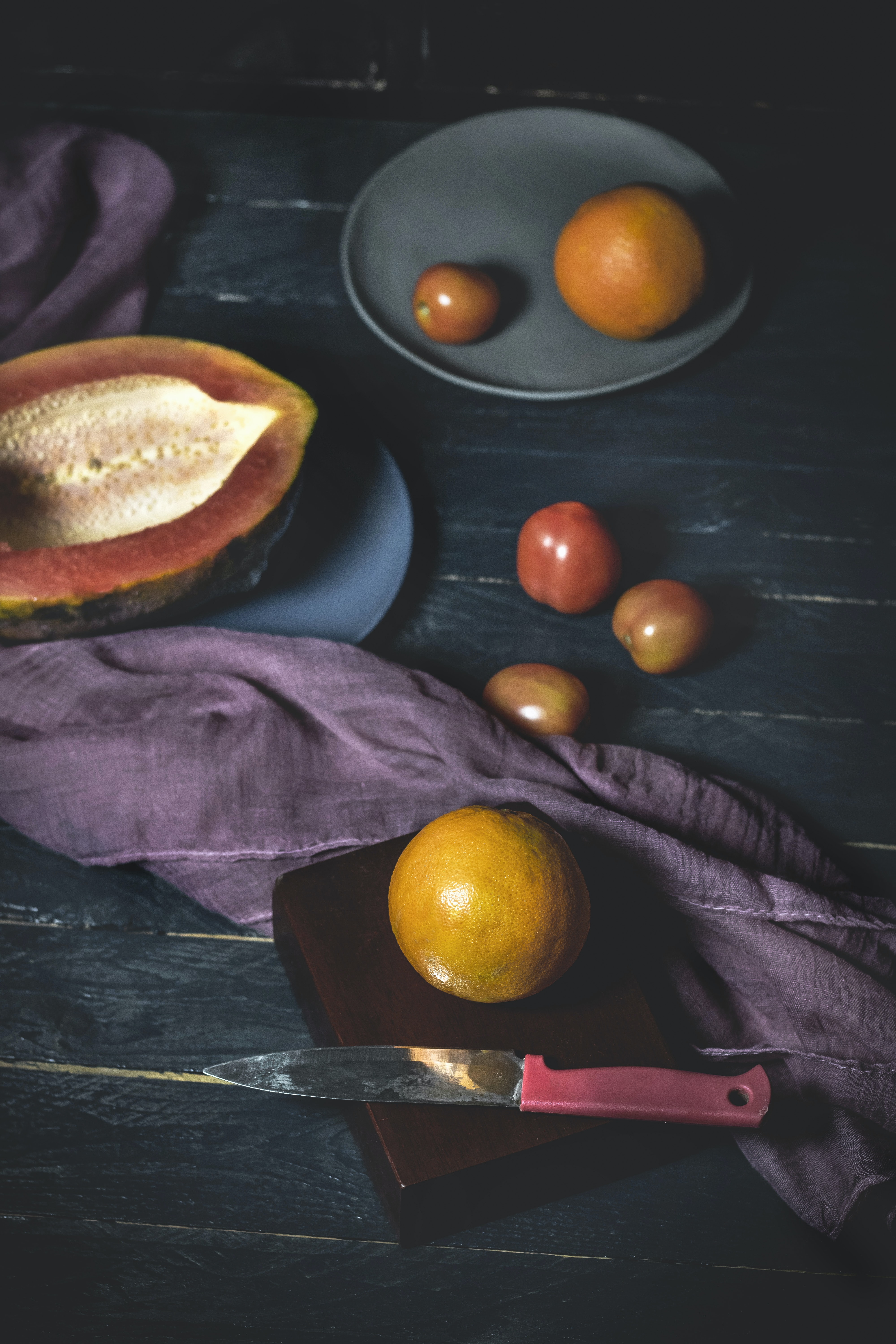 fruits near red and gray knife on wood
