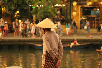 person standing and wearing conical hat vietnam teams background