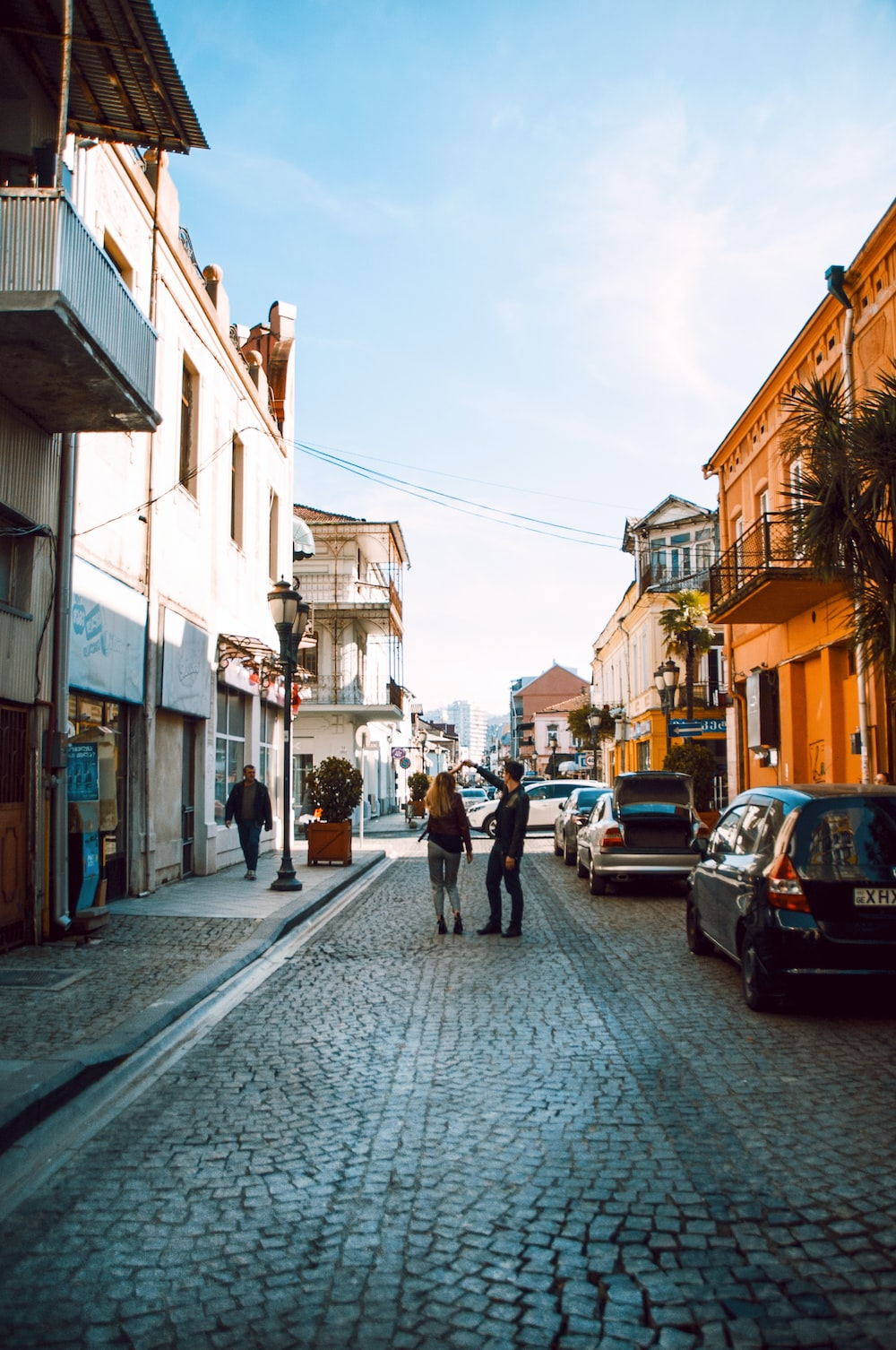 woman and man holding hands near buildings during daytime