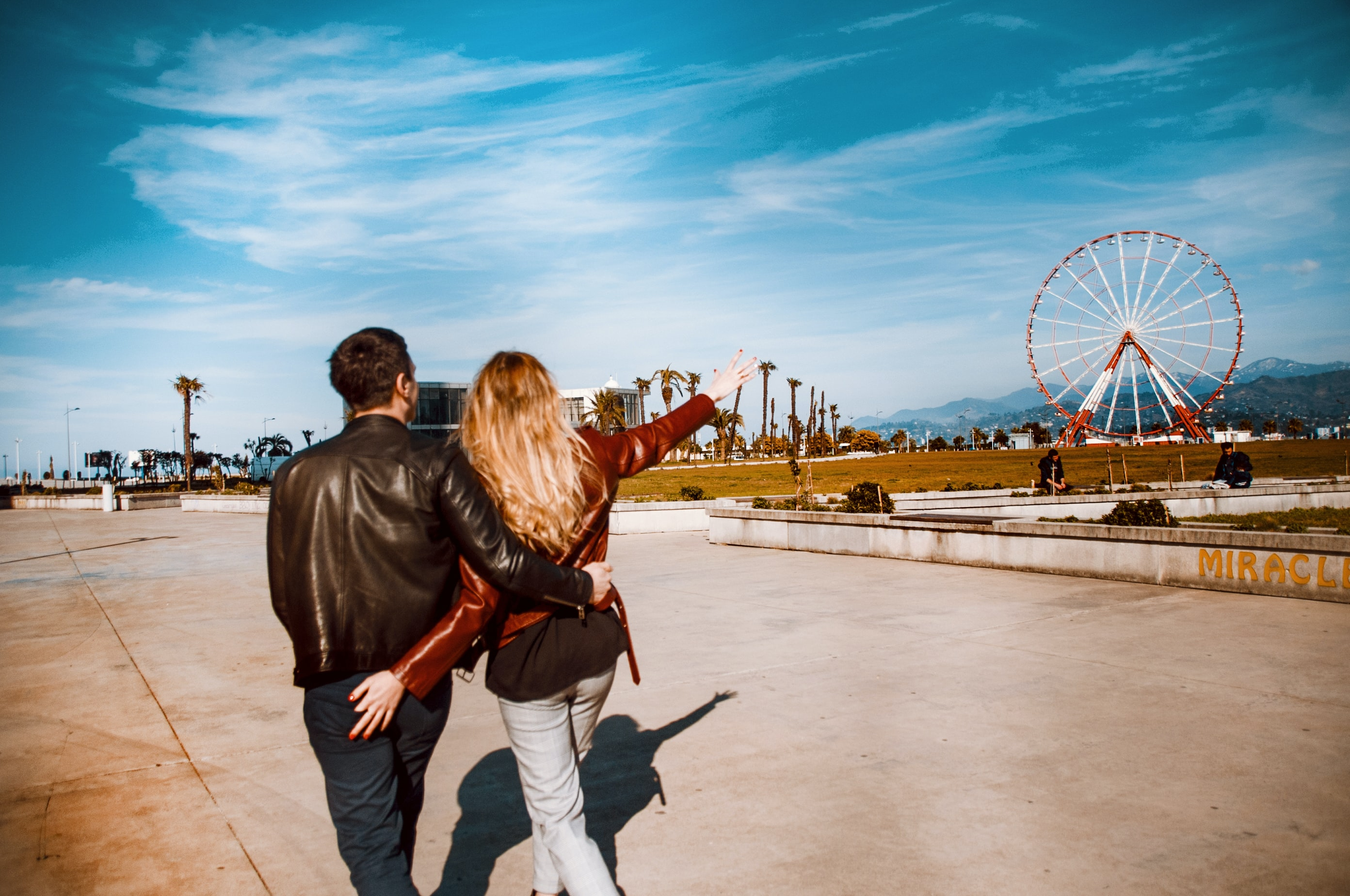 couple walking girl pointing red ferris wheel under blue sky and white clouds