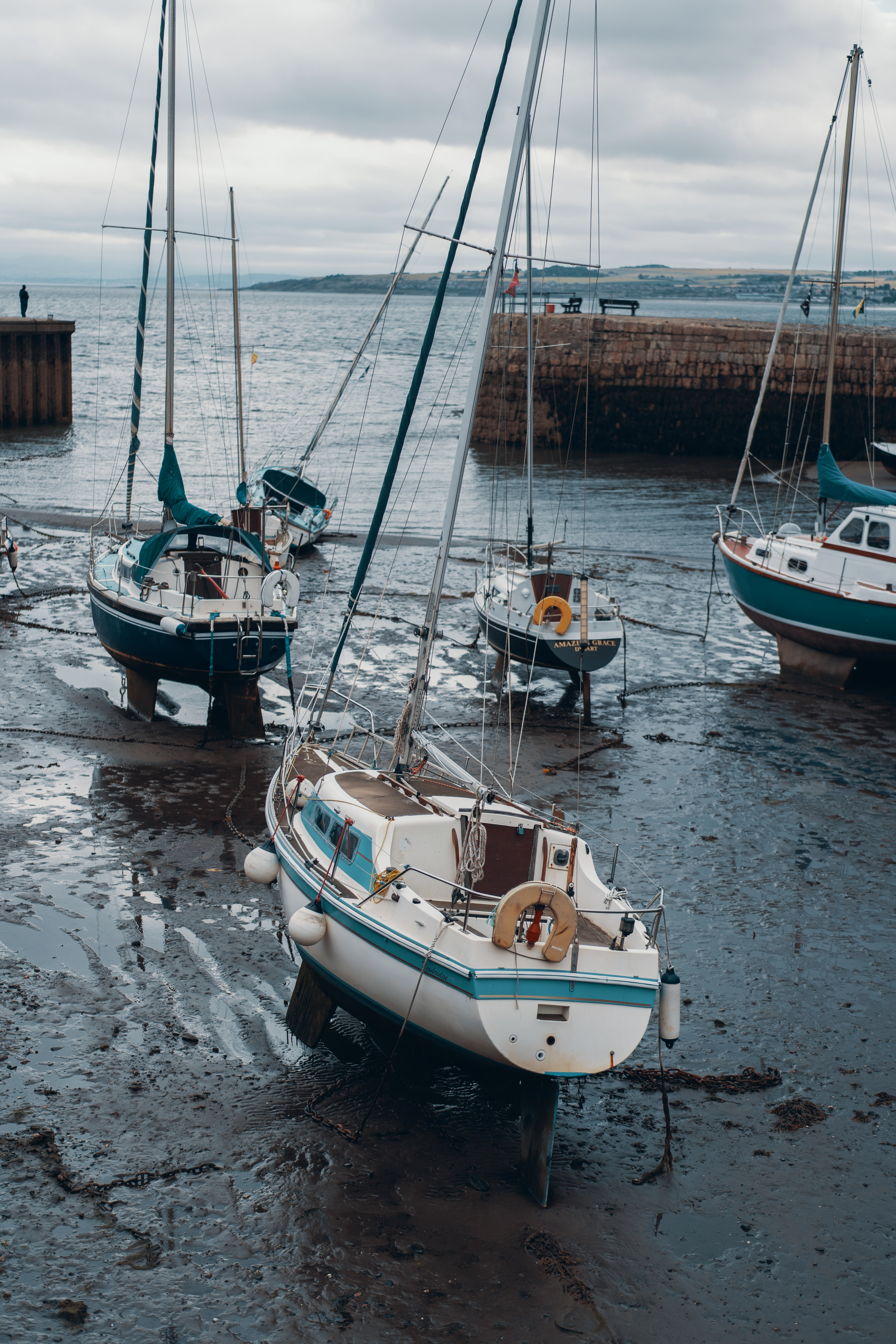 four fishing boats docked on gray sandy coast during daytime