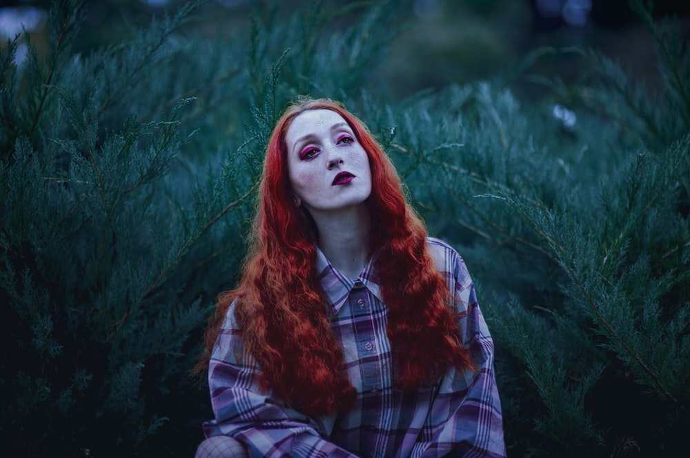 woman with red hair and red lipstick near green leafed plants