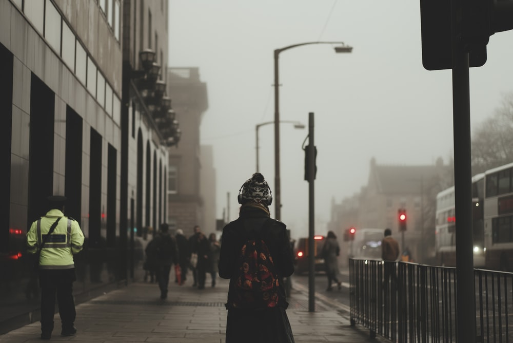 person wear black coat and backpack walking on sidewalk