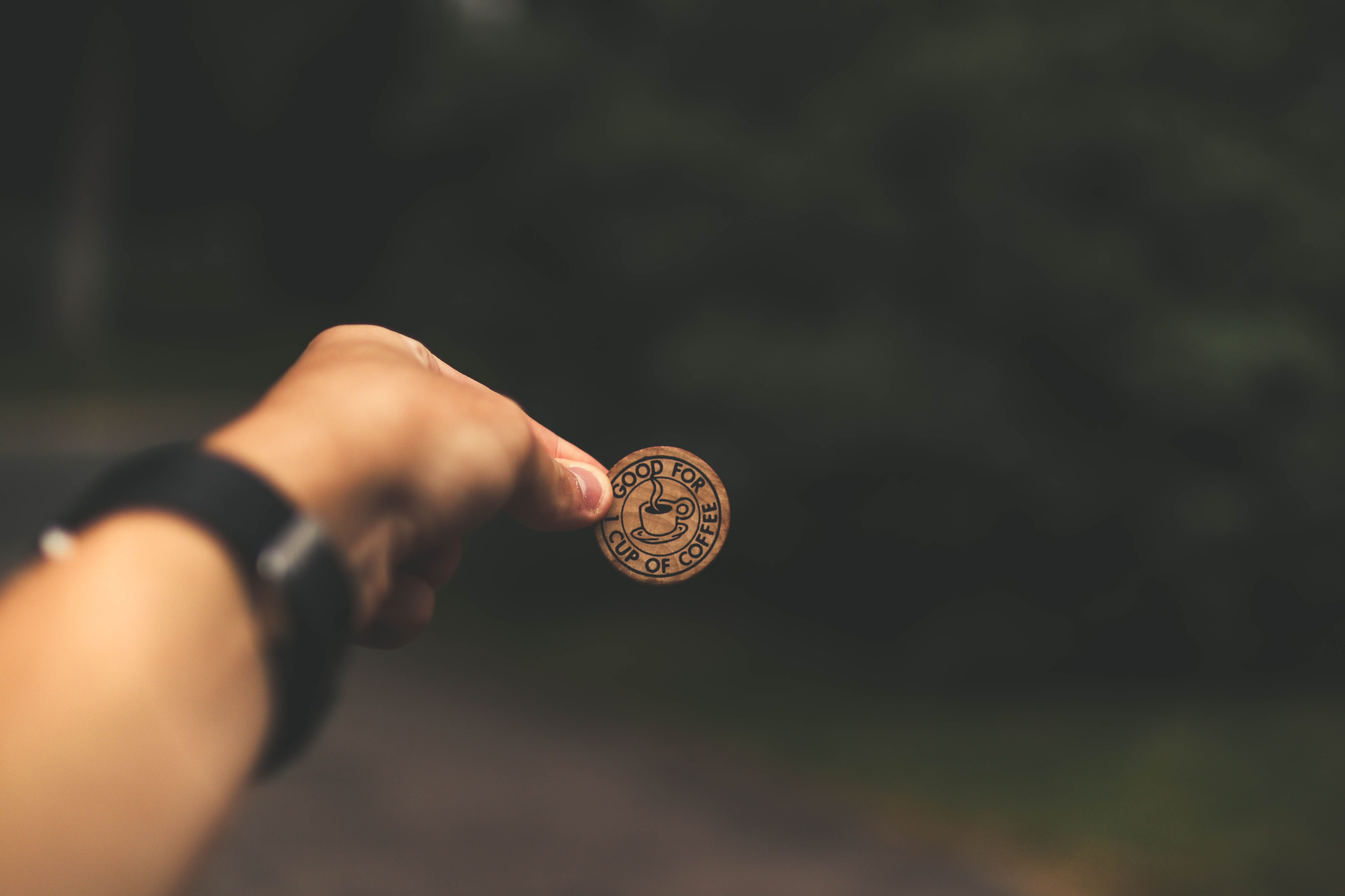 selective focus photography of man holding coin